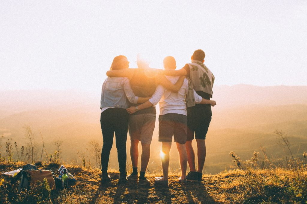 travel with friends: four young adults stand with their back to the camera on a hilltop overlooking the sunset