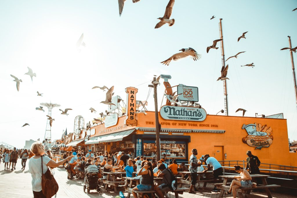 The famous Nathan's Hot Dogs at Coney Island Park for a New York Family Vacation with people seated at picnic tables and a lot of seagulls flying around. A great part of NYC itineraries