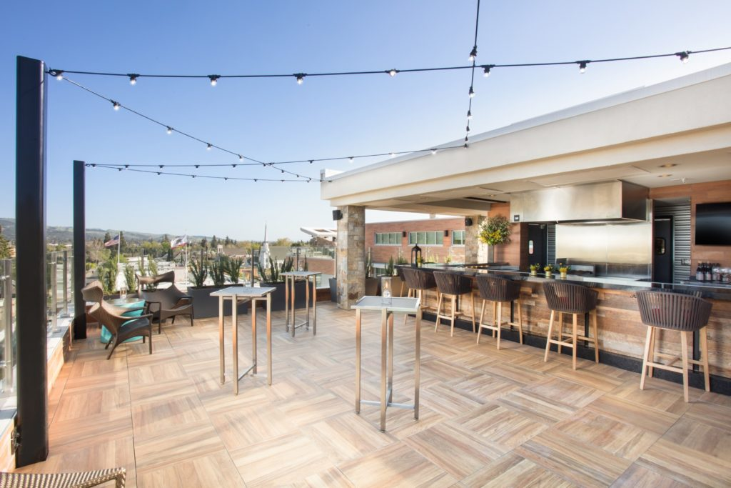 30th birthday trip ideas: Napa Valley photo of Archer Hotel rooftop with trendy design, crisscrossed twinkle lights, and light wooden floors