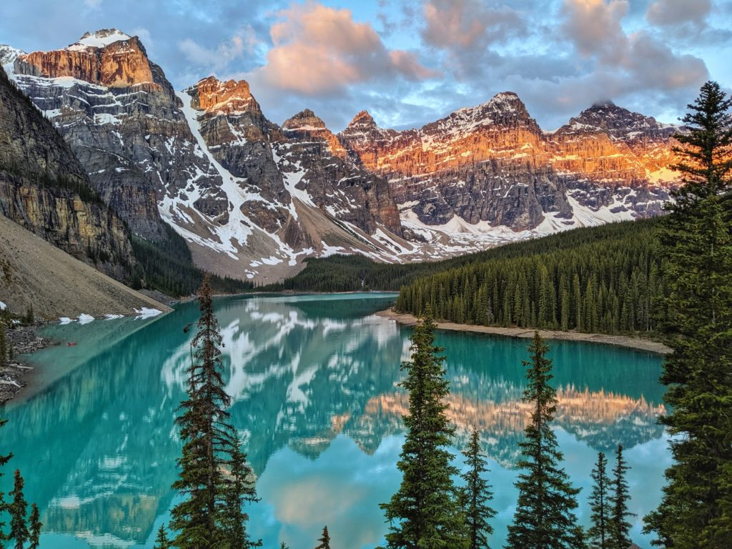 Mountains with snow in the background and bright blue lake with mountains and pine trees reflecting in the water