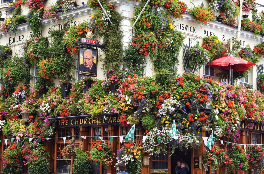 Outside view of The Churchill Arms bar in London covered in colorful flowers