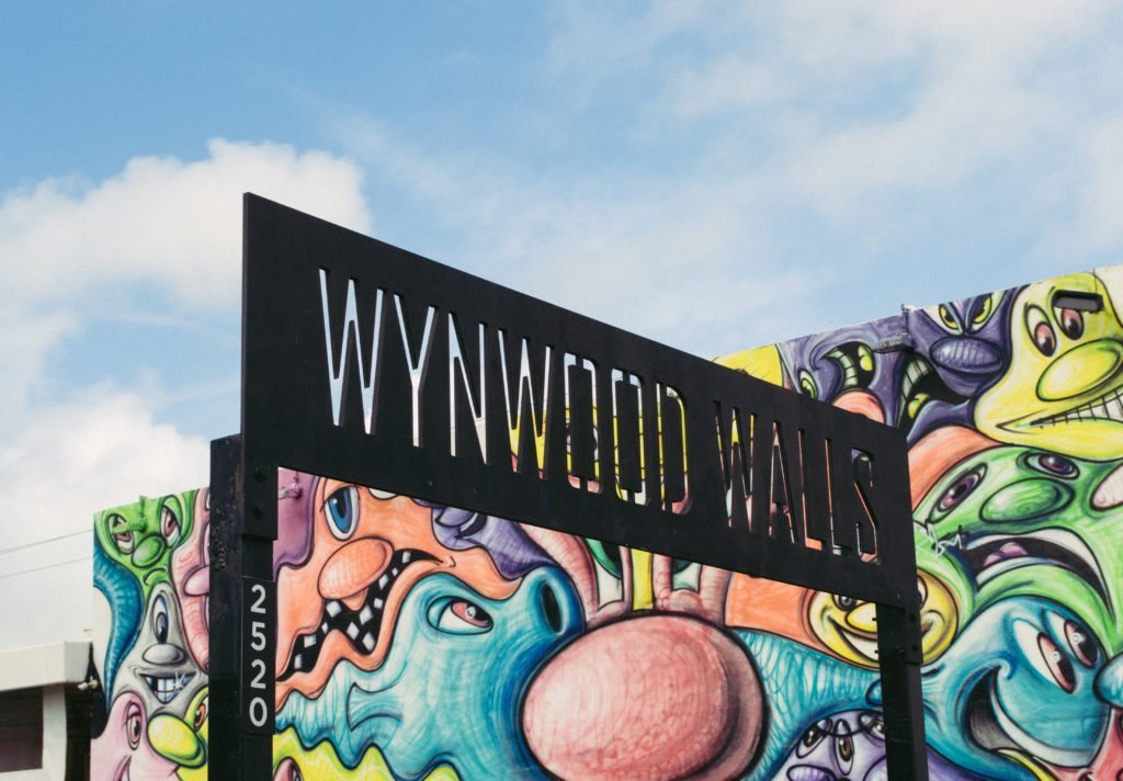 A colorful mural wall in the background with metal WYNWOOD WALLS sign in front