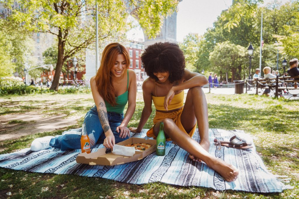 two girls smiling, sitting on a blanket sharing a pizza in Washington Square Park on a girls trip to NYC